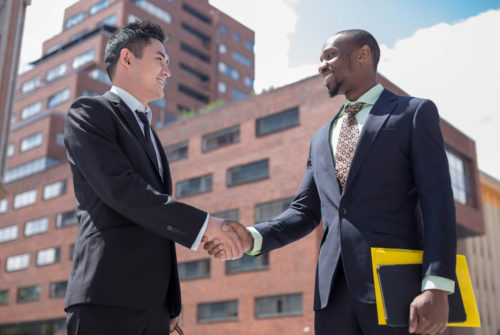 Portrait of multi ethnic business team .Two smiling men against the background of city. The one man is Chinese and African-American.