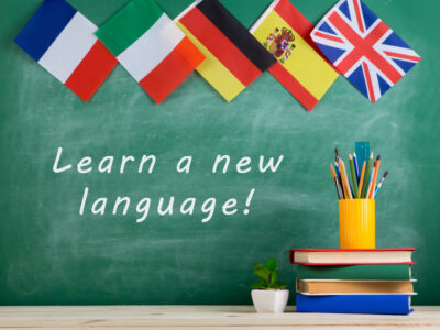 "Learning languages concept - flags of Spain, France, Great Britain and other countries, blackboard with text ""Learn a new language!"", books and chancellery"