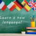 Learning languages concept - flags of Spain, France, Great Britain and other countries, blackboard with text